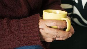 Kuvassa naisen kädet, ja käsien välissä kahvimuki