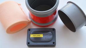 I mitten av bilden synns en fyrkantig svart dosa som det står önyland på. Dosan ligger framför en grå plastburk med röd tejp på sidan. Till höger om plastburken ligger ett grått lock och till vänster en skumgummibit.