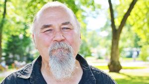 Närbild på en äldre man med grått skägg. Han står ute i en solig och grönskande park och ser glad ut.