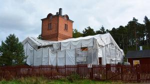 En röd tegelbyggnad med ett torn. Taket är täckt med vita presenningar.