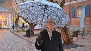En dam med leopard-mönstrat paraply står i Gamla stan i Borgå.
