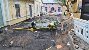 En gränd i Gamla stan i Borgå har grävts upp. Två personer i hjälmar och gula västen gräver i den stora gropen mellan husen. Stora rör går tvärs över gropen.