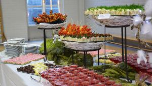 På ett bord står skålar och fat fyllda med sötsaker och små salta bitar. Vinglas är fyllda med röd saft.