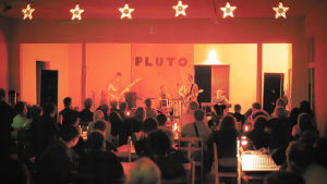 After Eightin järjestämä Pluto-festivaali. Ihmisiä istuu hämärässä kahvilassa kuuntelemassa Crash-yhtyettä vuonna 1998.