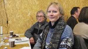 En äldre kvinna och en äldre man sitter vid ett bord. Framför sig har de papper och kaffekoppar.