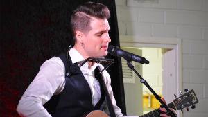 En man med vit kragskjorta och väst står på en scen. Han håller i en gitarr och sjunger i en mikrofon.