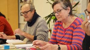 En kvinna och en man sitter bakom pulpeter och jobbar med läroböckerna framför sig.