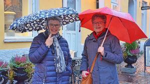 Två damer står bredvid varandra under sina paraplyer och ler.