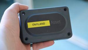 En hand håller i en svart plastdosa. På dosan finns en gul tejpbit och på den står det önyland.