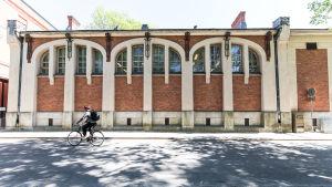 En person cyklar förbi Katedralskolans gymnastiksal, där arkeologiska utgrävningar görs.
