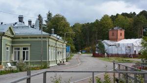 Till vänster syns ett stort grönt hus, den gamla järnvägsstationen. På andra sidan vägen, till höger, finns ett tegelhus med ett torn. Taket är intäckt med vita presenningar.