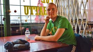 En ung man sitter vid ett bord på en bar. Han vilar kinden mot handen och tittar in i kameran. Framför honom ligger en mössa och står en vattenflaska.