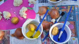 På ett underlag av tidningspapper ligger lökgalvor, potatishalvor och blomkålsbitar. Bland dem finns någraplastbyttor med färg, penslar och var sin potatishalva.