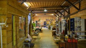En stor träbyggnad inifrån. Man ser olika antik- och prydnadsföremål i rummet.