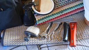 På en soffa finns flera verktyg prydligt uppradade: en borste, saxar och trimmrar. Ovanför dem finns en svart sprutflaska och en liten spegel.