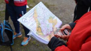 Närbild på en orienteringskarta och en kompass som någon i röd jacka håller i.