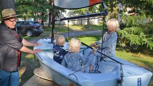 En man står bredvid en liten segelbåt. Segelbåten står i en park och tre små barn sitter i den.