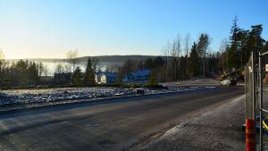 En asfalterad väg leder ner mot några trähus. Nära fotografen, i högra hörnet av bilden, finns ett stängsel runt en byggplats. I fjärran, bakom trähusen, syns Borgå å.