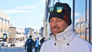 En medelålders man i mössa och vit jacka tittar in i kameran. Bakom honom syns Borgå centrum.