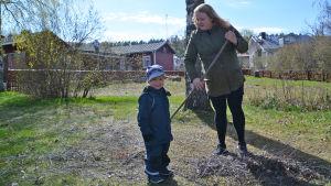 En kvinna krattar. Framför henne står en liten pojke och tittar in i kameran.