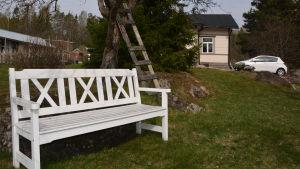 I förgrunden synns en vit träbänk i en trägård. Bakom den ett trähus och en vit bil.