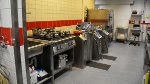 Interiören i ett kök. Man ser många kastruller och stora köksmaskiner.