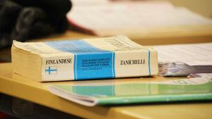 En finsk-italiensk ordbok på en pulpet.
