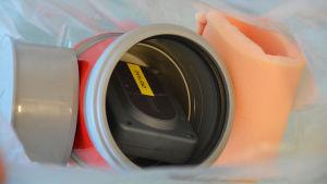 I mitten av bilden synns en fyrkantig svart dosa som det står önyland på. Dosan ligger inuti en grå plastburk med röd tejp på sidan. Till vänster om plastburken ligger ett grått lock och till höger en skumgummibit.