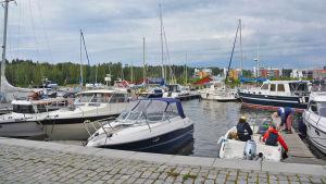 På bilden syns flera rader med segelbåtar och motorbåtar i Borgå å. Längst nere till höger i bilden finns en öppen motorbåt med några personer i. En man håller på att förtöja båten.