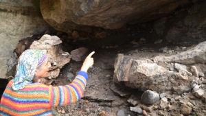 En medelålders man i randig tröja och duk om huvudet står framför en låg grottöppning. Han pekar inåt grottan.
