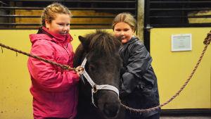 Två flickor står på var sida om en svart ponny.