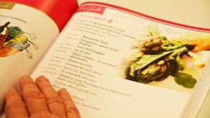 En lärobok i italienska är uppslagen och en hand håller upp den. På sidan till höger finns en bild på en grönsak.