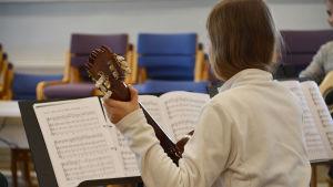 En flicka spelar gitarr.