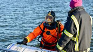 En dykare i orange dräkt vid vattenytan tillsammans med en annan person i svart jacka.