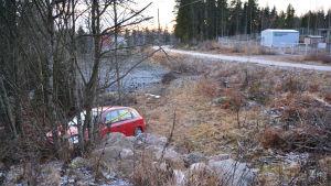 En liten röd bil med framändan på en stenhög på en åker. Bilen är lite tillknycklad framtill och har ett gult plastband om sig. Bakom bilen syns vägen en bit bort.