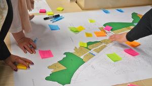 På bilden syns en ritning av bostadsområdet. Utanpå det har någon fäst post-it lappar med kommentarer. Flera personer har sina händer på pappret.