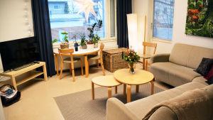 Bild av ett vardagsrum i ljusa färger. En beige hörnsoffa och några runda bord finns framför en television. I fönstret hänger en julstjärna.