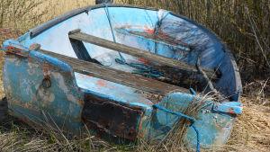 En väderbiten blå roddbåt ligger i strandgräset.