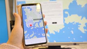 En hand håller i en smarttelefon med en karta på skärmen. Bakom handen och telefonen syns en dator med en karta på skärmen.