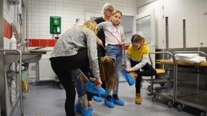 Fyra flickor och en kvinna står i ett kök och klär på sig blå plastskydd på skorna.
