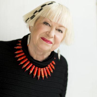 Porträtt på Maikki Harjanne, en 70plussare med vitt kort hår, läppstift.