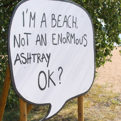 en stor skylt påminner om att stranden inte är en askkopp