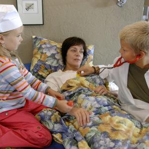 Kotikadun Eeva (Lena Meriläinen) makaa sängyssä. Häntä hoitavat lääkärileikissä Kerttu (Linda Liikka) ja Jarkko (Santeri Nuutinen).