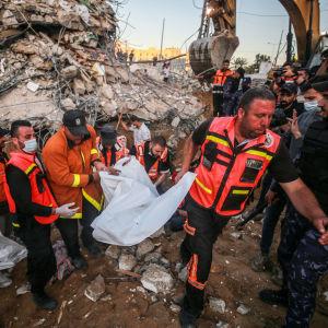 Palestiinalaiset pelastustyöntekijät kantavat pommituksissa kuollutta pois raunioista Gazassa 13.5.2021.