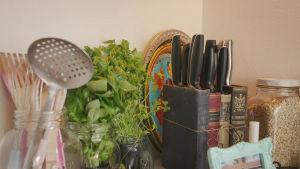 Pöydällä leikkuuveitsiä vanhoista kirjoista tehdyssä veitsitelineessä, muita keittiövälineitä ja yrttejä ruukuissa.