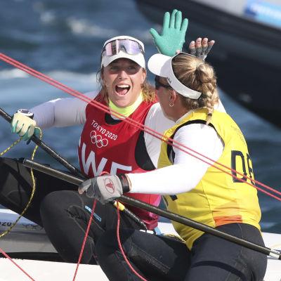 En seglare i röd väst och en seglade i gul väst ger varandra en high-five till havs.