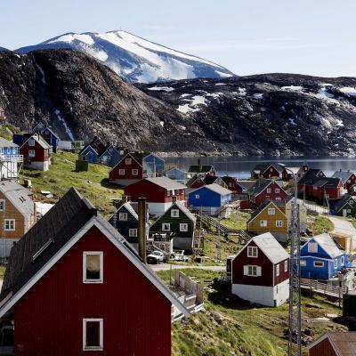 Grönland. I förgrunden syns färglada villor rymligt utplacerade i en grön slänt. I bakgrunden syns snötäckta majestätiska berg.
