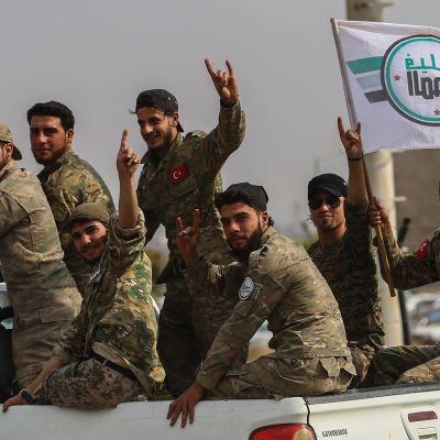 Sotilaita avolava-auton kyydissä.