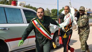 Iranska soldater bär bort en sårad kamrat efter attacken mot en militärparad i Ahvaz, lördagen 22.9.