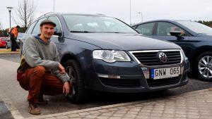 Ville Laitinen sitter på huk bredvid sin gasbil.